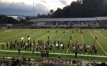 Middle School musicians participating with the Varsity Marching Band prior to a football game
