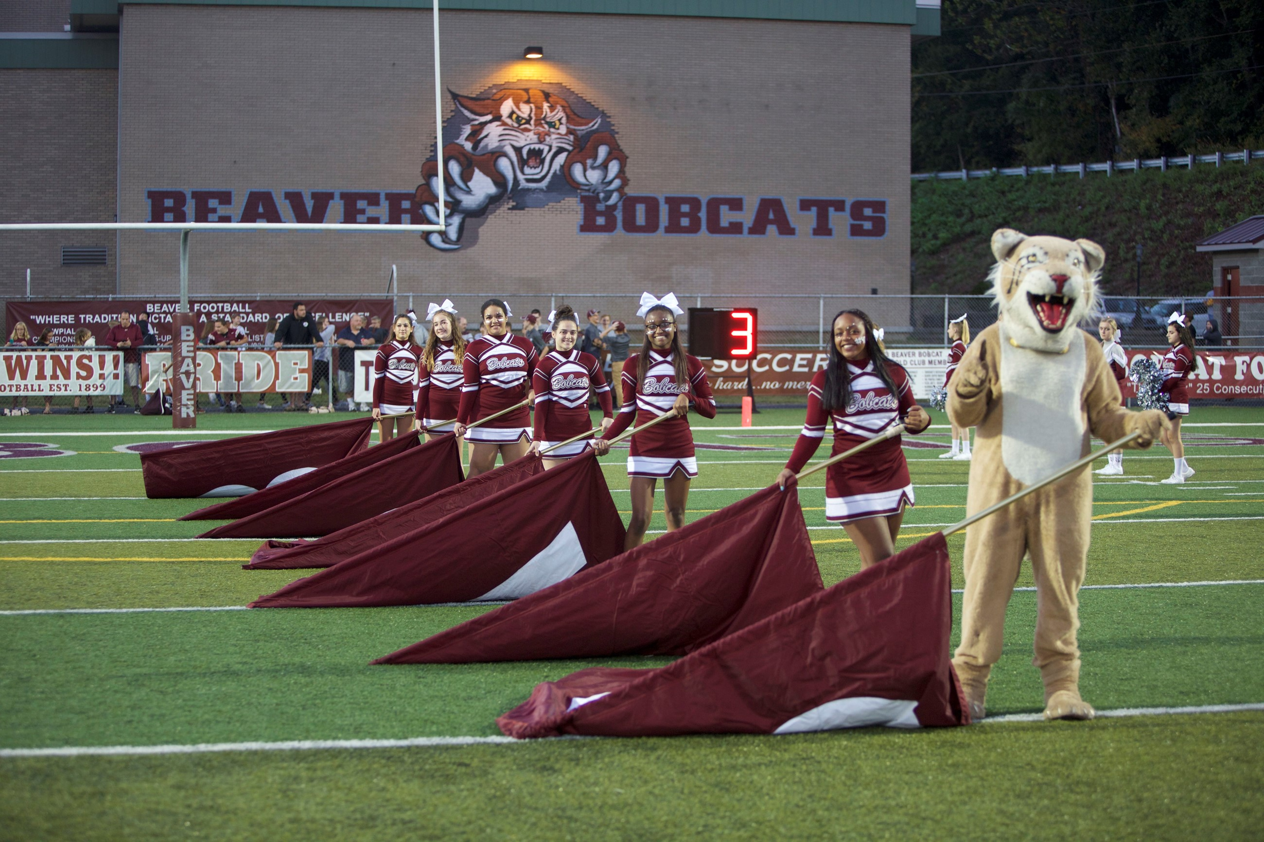 Cheerleaders and Bobcat mascot with flags prior to the start of the Homecoming football game