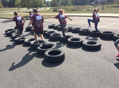 Dutch Ridge students jumping through tires on the obstacle course during Jog-a-Thon