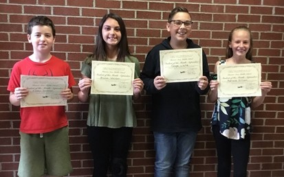 Four Middle School Students of the Month holding their certificates