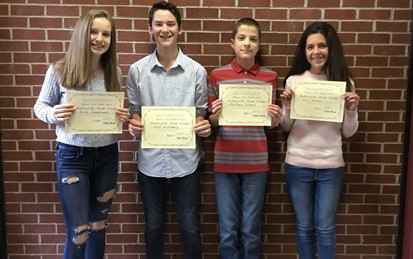 Four Students of the Month for October holding certificates