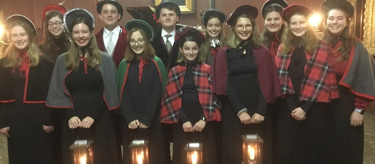 12 members of Chamber Choir carolling at Merrick Art Gallery in period costumes