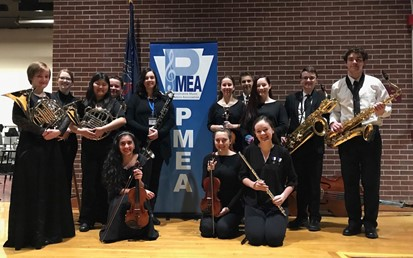 Thirteen students holding musical instruments in front of a PMEA banner