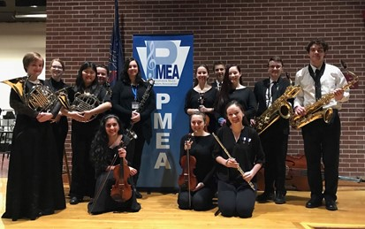 Thirteen students holding musical instruments standing in front of a PMEA banner
