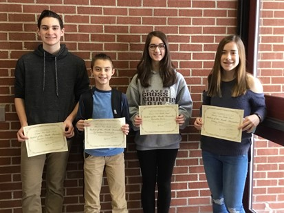 Four Middle School students of the month for January 2018 holding certificates