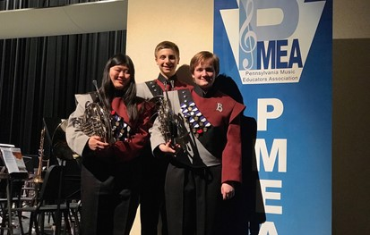 Three students holding musical instruments in front of a PMEA banner