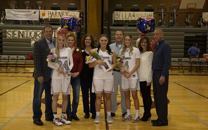 Three girls basketball players and their parents on Senior Night