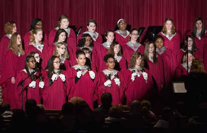 Five members of Concert Choir holding handbells along with 21 vocalists at the Winter Concert