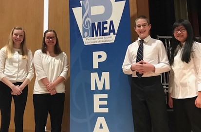 Four students posing with PMEA Banner at District Band Festival
