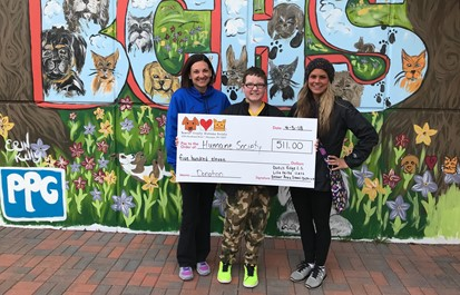 Two teachers and student holding check for donation to Humane Society