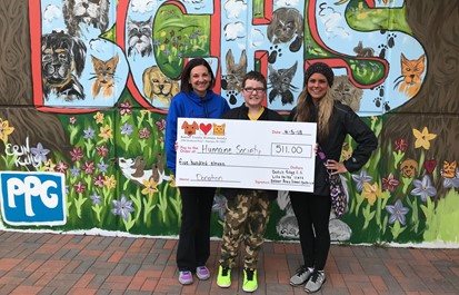 Two teachers and a student holding a check for donation to Humane Society