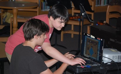 Two students working on technology at Middle School Coffee Shop Night