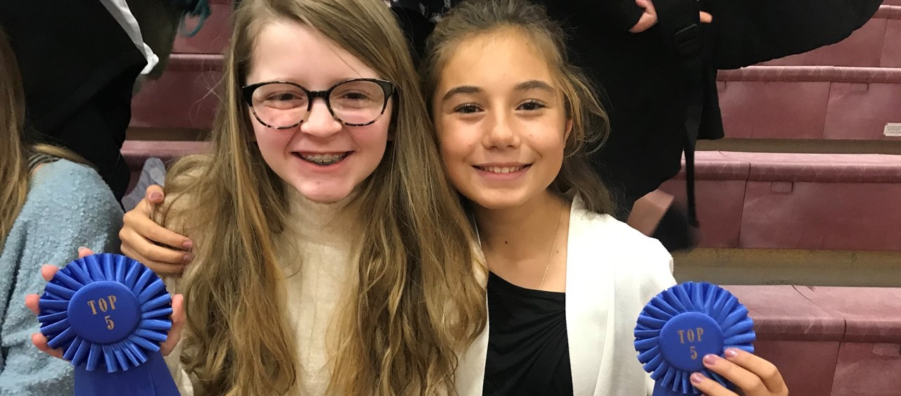 Two middle school students holding blue ribbons for Forensic Tournament