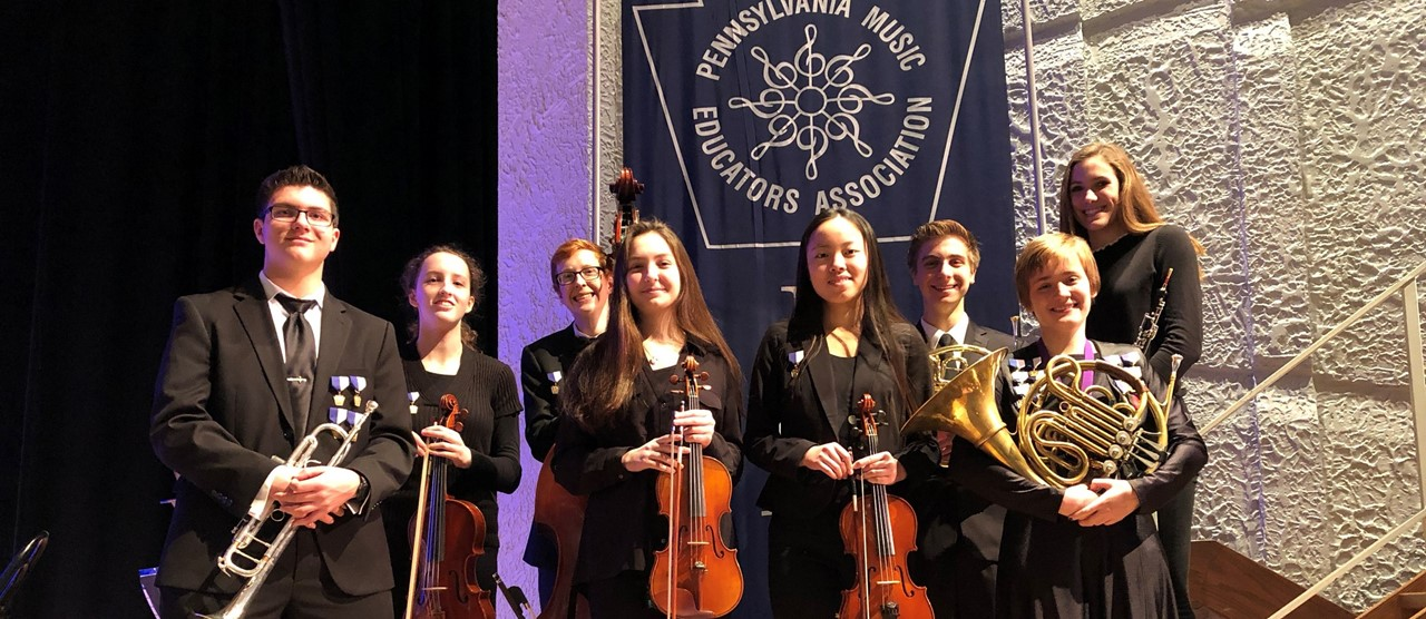 Eight students holding their instruments at the PMEA Orchestra Festival in Erie, PA