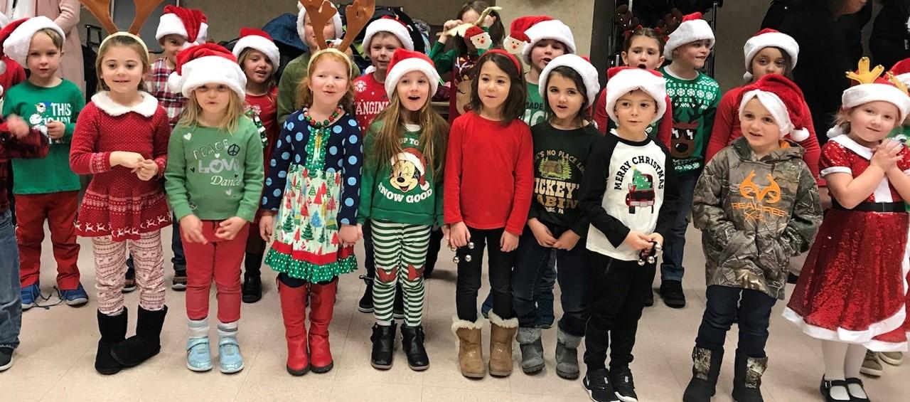 Kindergarten students in holiday attire and santa hats caroling at King Beaver Apartments