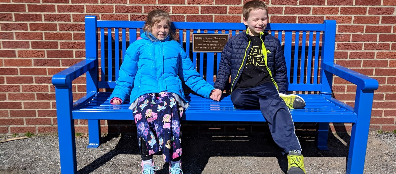 Two elementary students sitting on the Buddy Bench at College Square