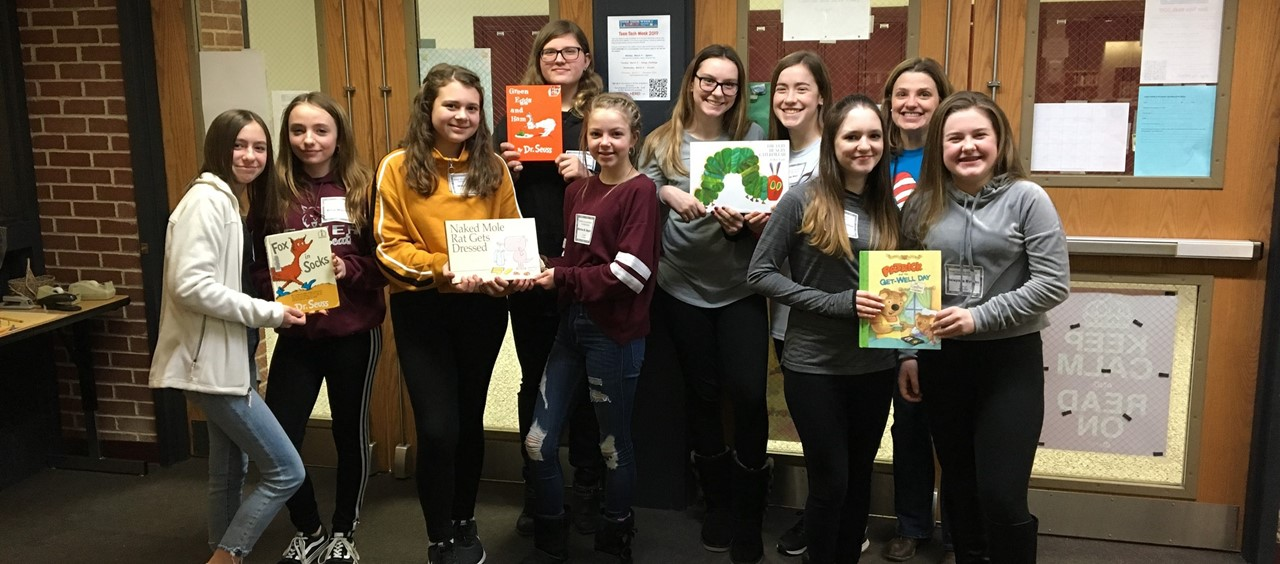 Nine students and librarian holding books for Read Across America to be read to the elementary students