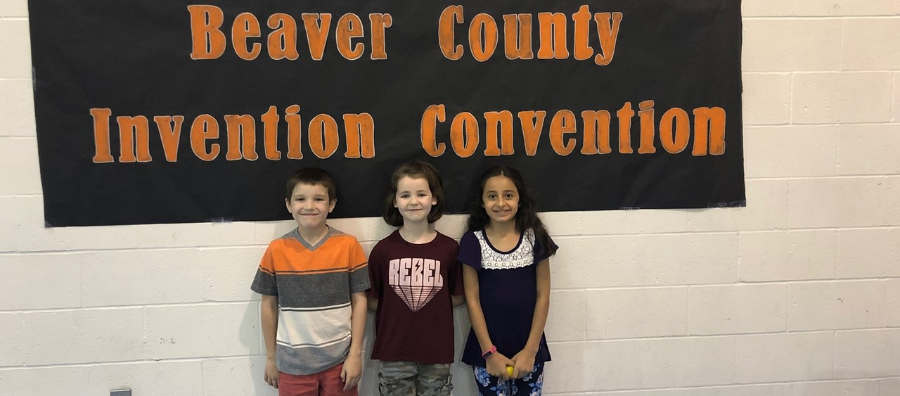 Three elementary students under Beaver County Invention Convention Banner