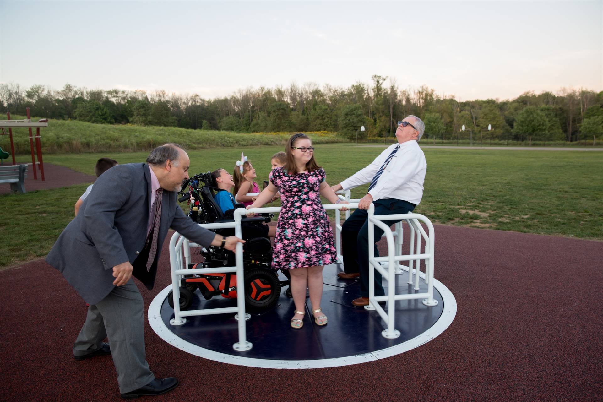 Dr. Guzzetti pushes the merry-go-round while Hon. Tim Finn and kids enjoy the ride