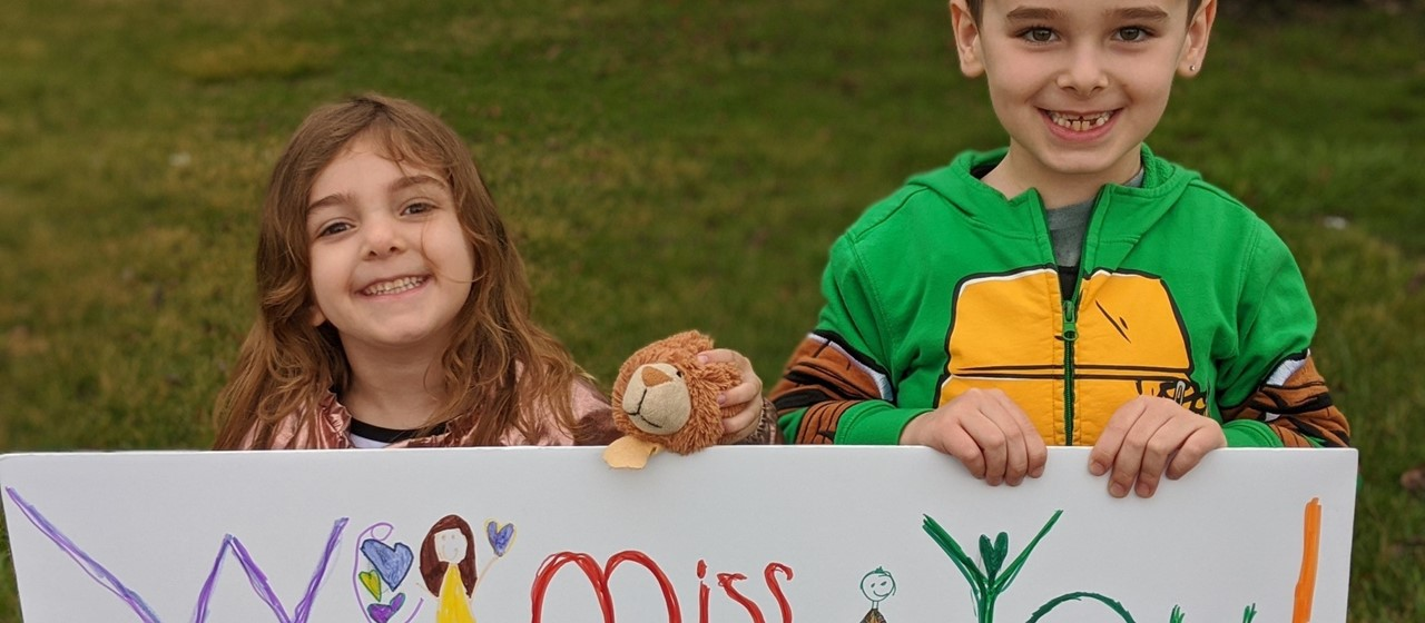 Two kids holding a We miss you sign at the BASD Staff Parade on 3/28/20